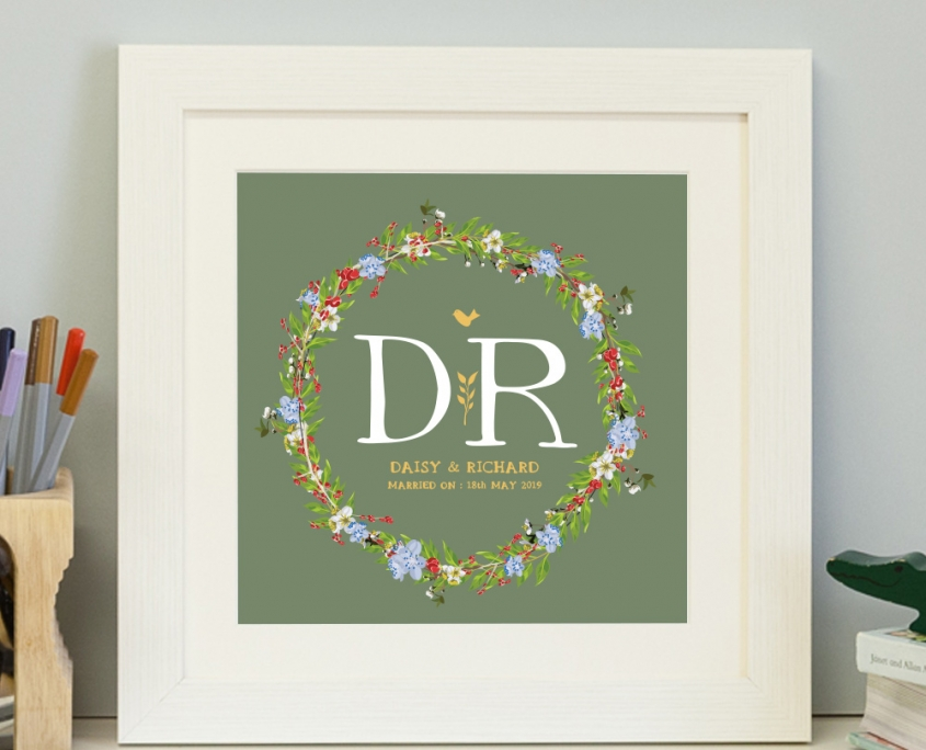 A personalised initial print with a floral garland design in a white frame with sage green background